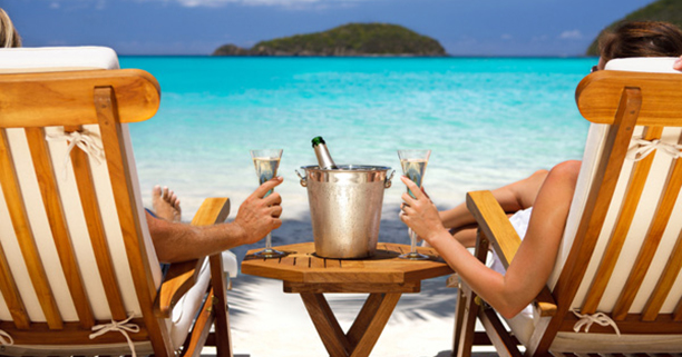 honeymoon couple in recliners drinking champagne at a Caribbean
